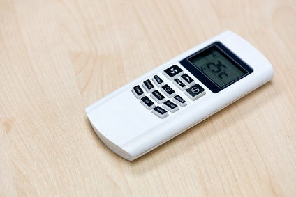 Air condition remote on the wooden table in the meeting room and setting temperature at 25 degree celcius.
